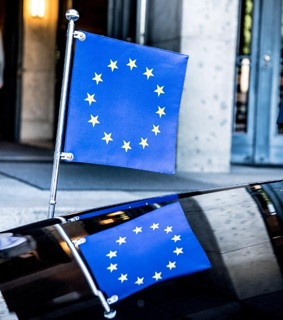 The miniature of the European flag and its reflection on the bonnet of a car