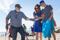 Frans Timmermans, on the left, picks up plastic trash on the beach.